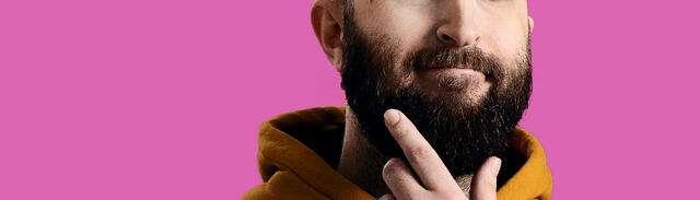 Man med skägg kliar sig på hakan